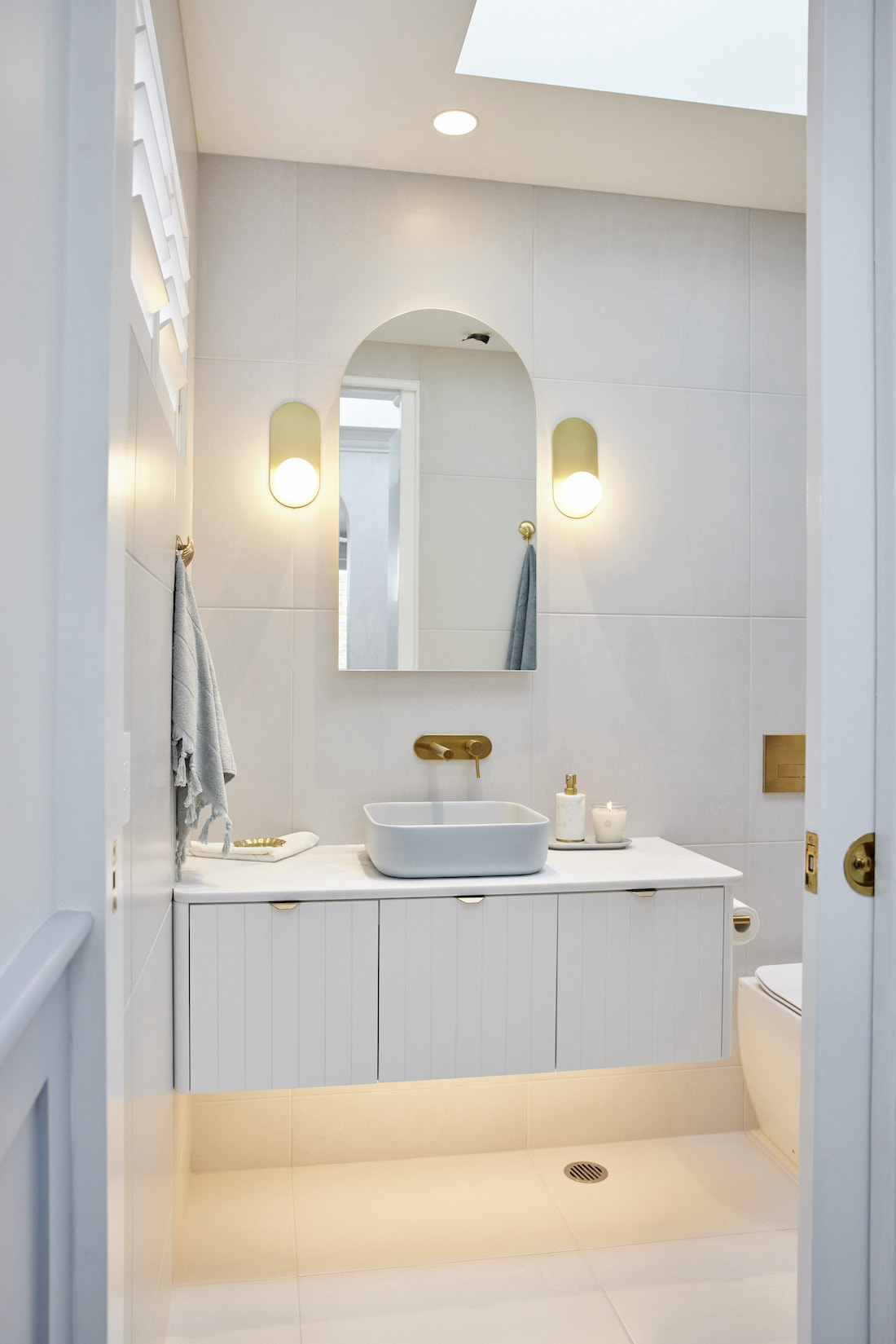 White bathroom with blue sink and arch mirror