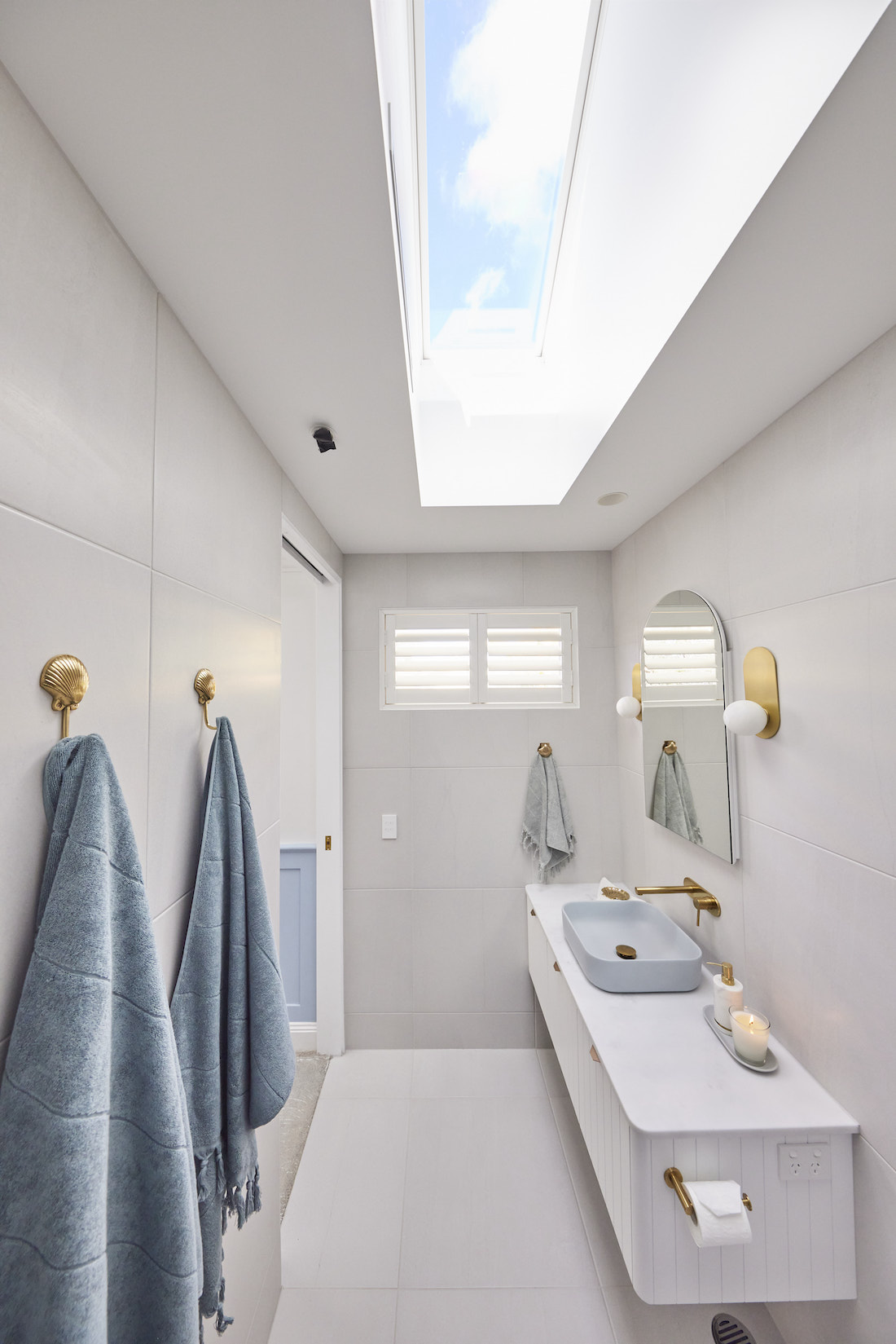 Skylight in narrow blue and white bathroom