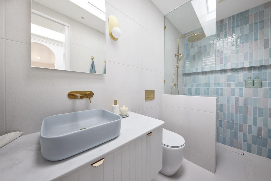 Blue tiled shower in bathroom