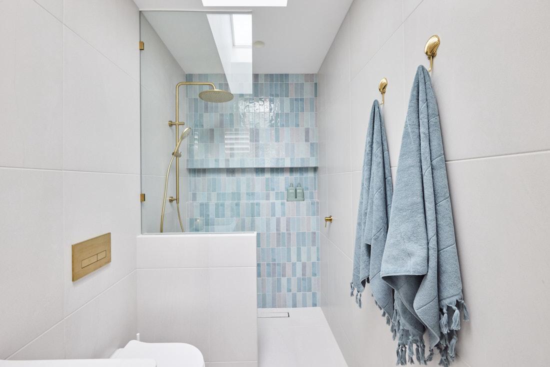 Blue tiled shower in ensuite bathroom