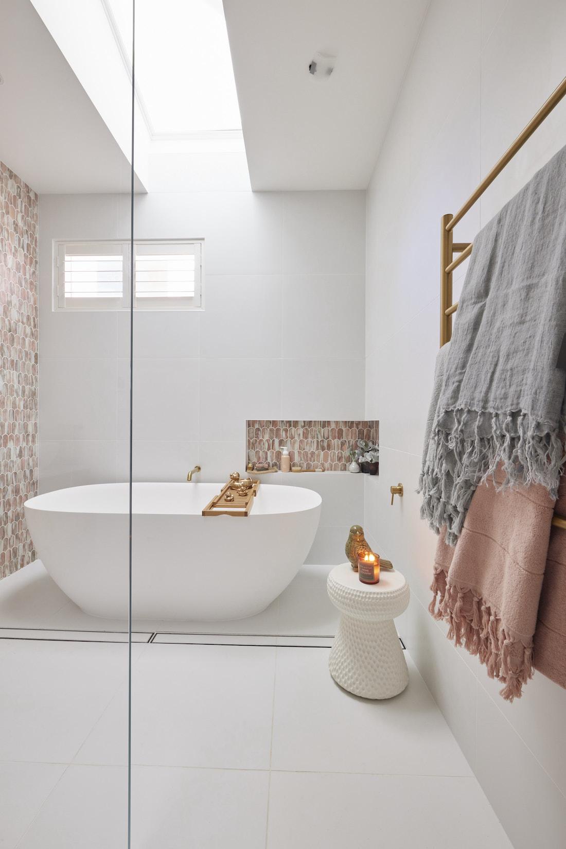 Freestanding matte white bath in pink bathroom