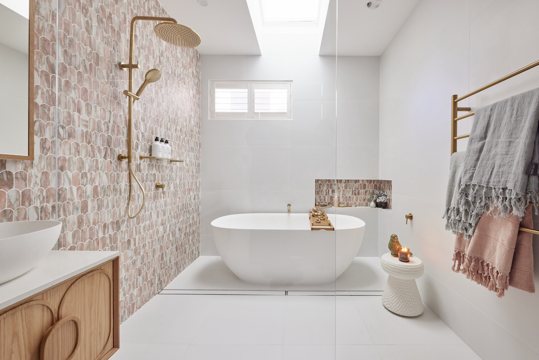 Pink and white bathroom with aged brass accents