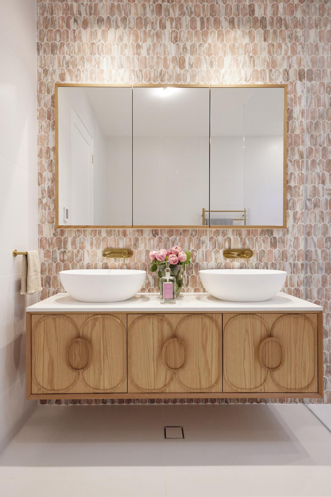 Floating timber vanity in pink tiled bathroom