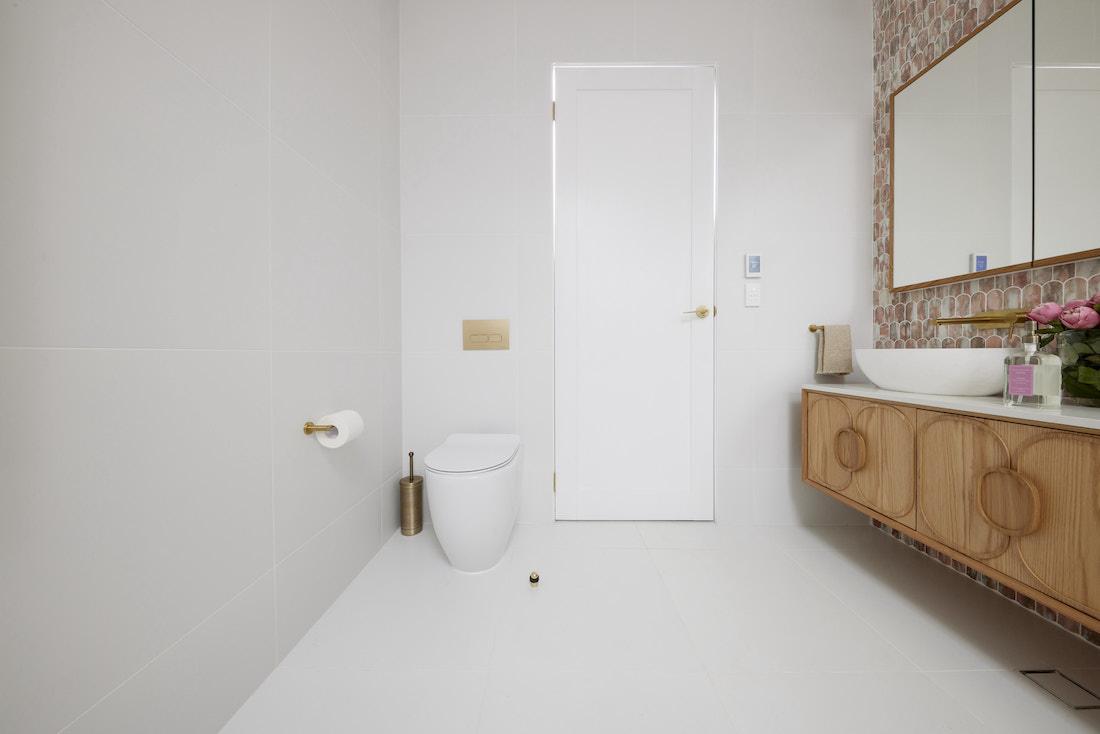 Toilet tucked behind door in guest ensuite bathroom
