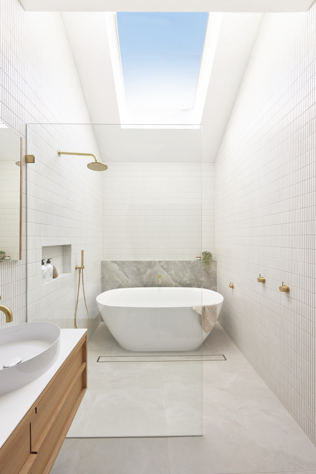 White bathroom with skylight and freestanding curved bath
