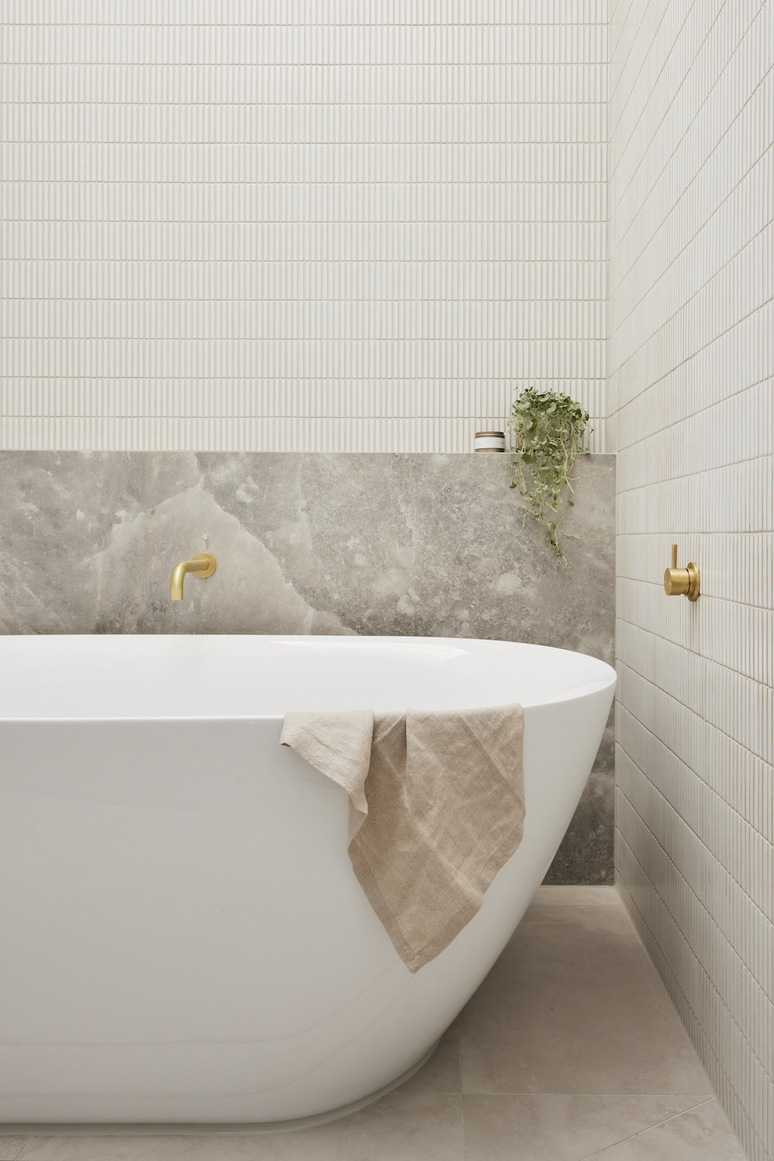 Curved bath with marble look tiles and white kit kat tiles