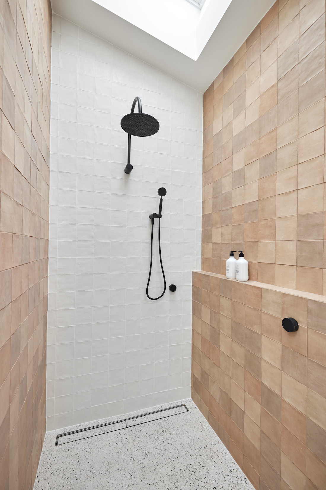 Black rain shower in white and brown shower with skylight
