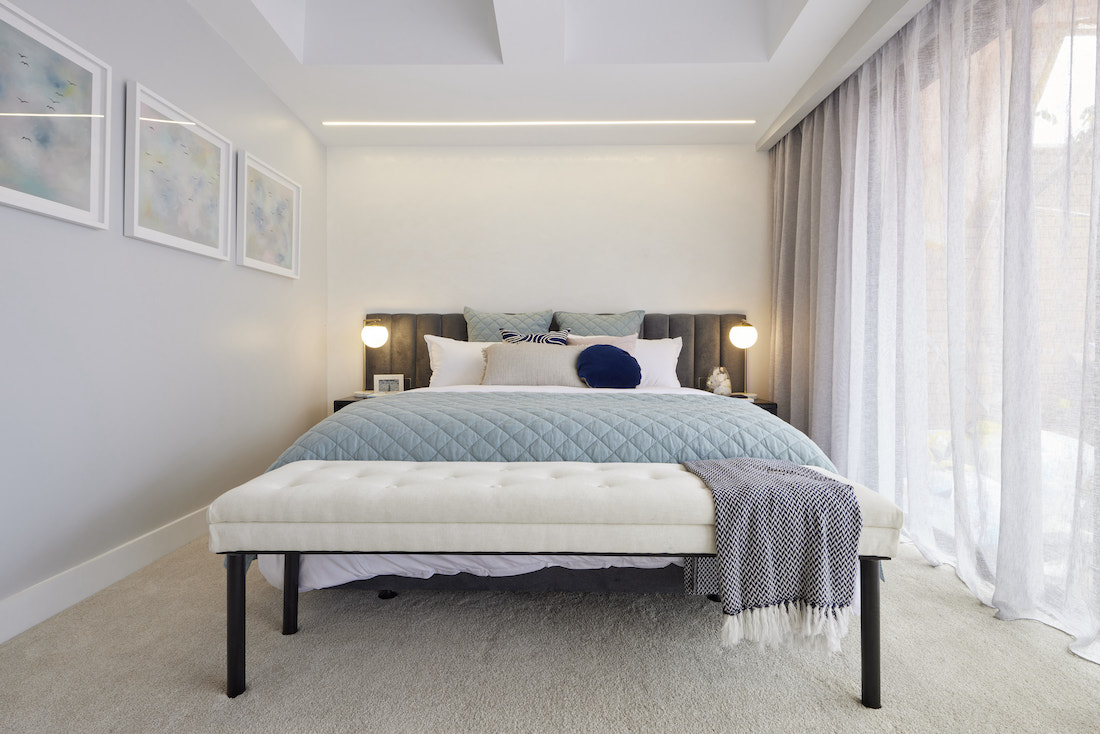 Master bedroom with blue throw on bed
