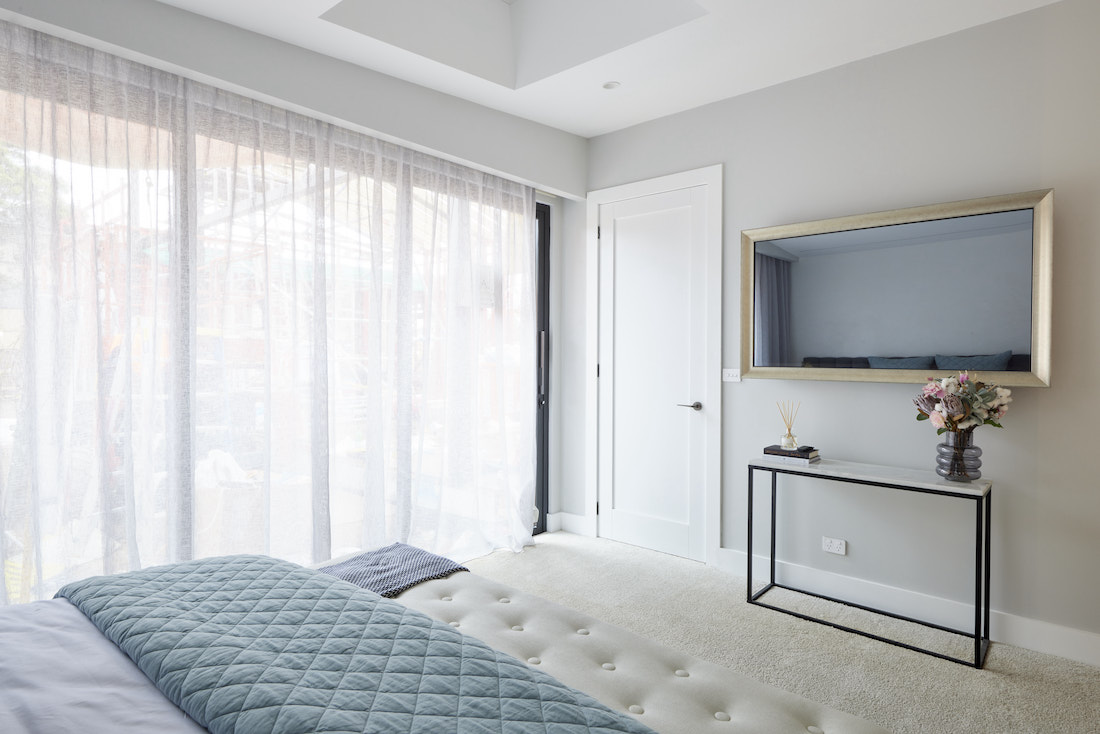 Black framed side table and sheer curtains in master bedroom