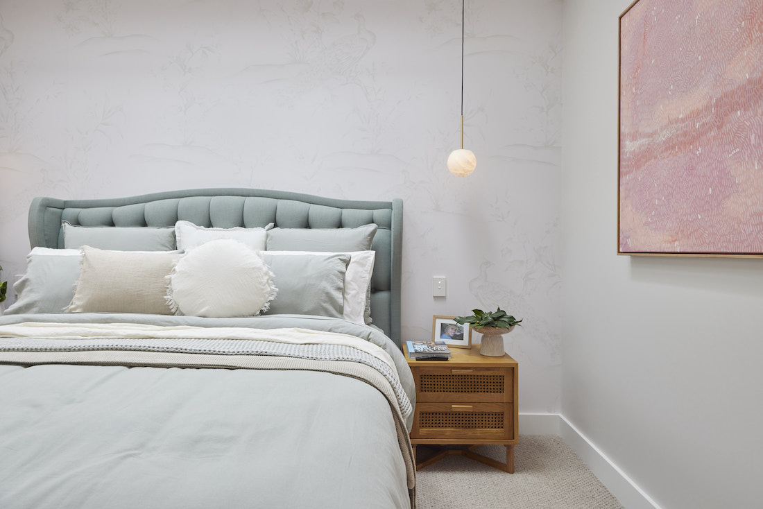 Sage green padded bedhead with neutral toned bedding