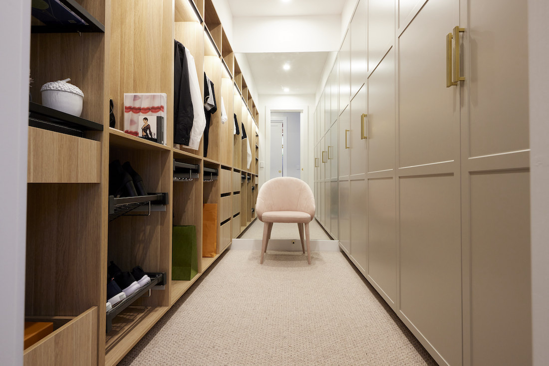 walk in wardrobe with timber open shelving and pink velvet chair