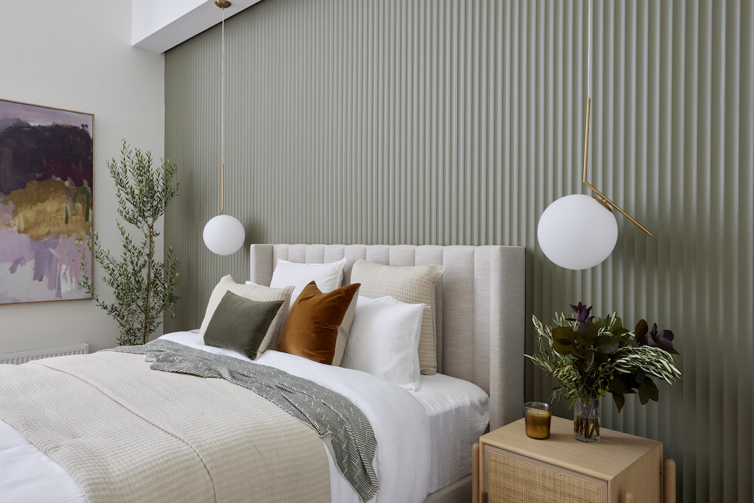 Master bedroom with sage green fluted feature wall