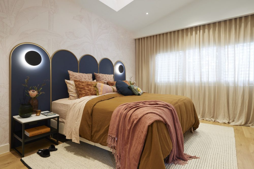 Tan and blue master bedroom with sheer curtains