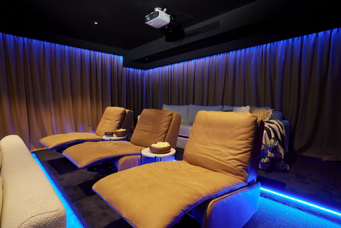 Recliners in home cinema with blue LED lights