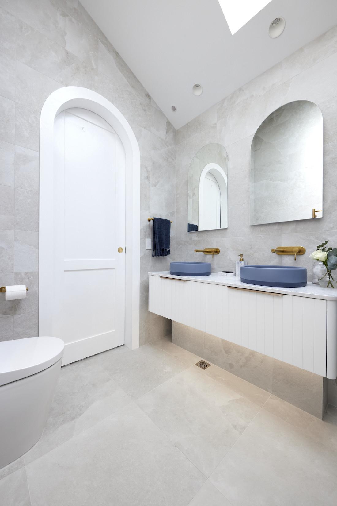 Arch doorway in bathroom with indigo blue basins