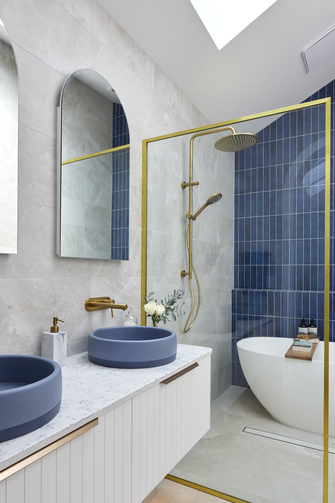 Indigo blue tiled feature wall with gold accents in bathroom
