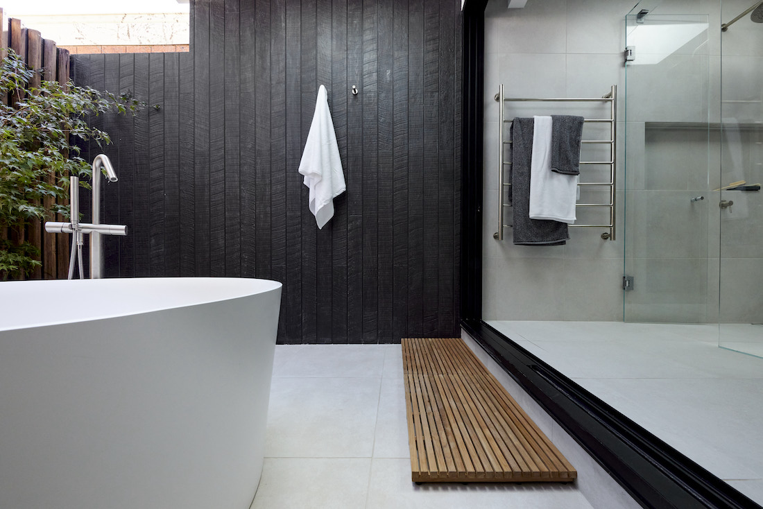 Outdoor bath with timber bathmat and black timber wall
