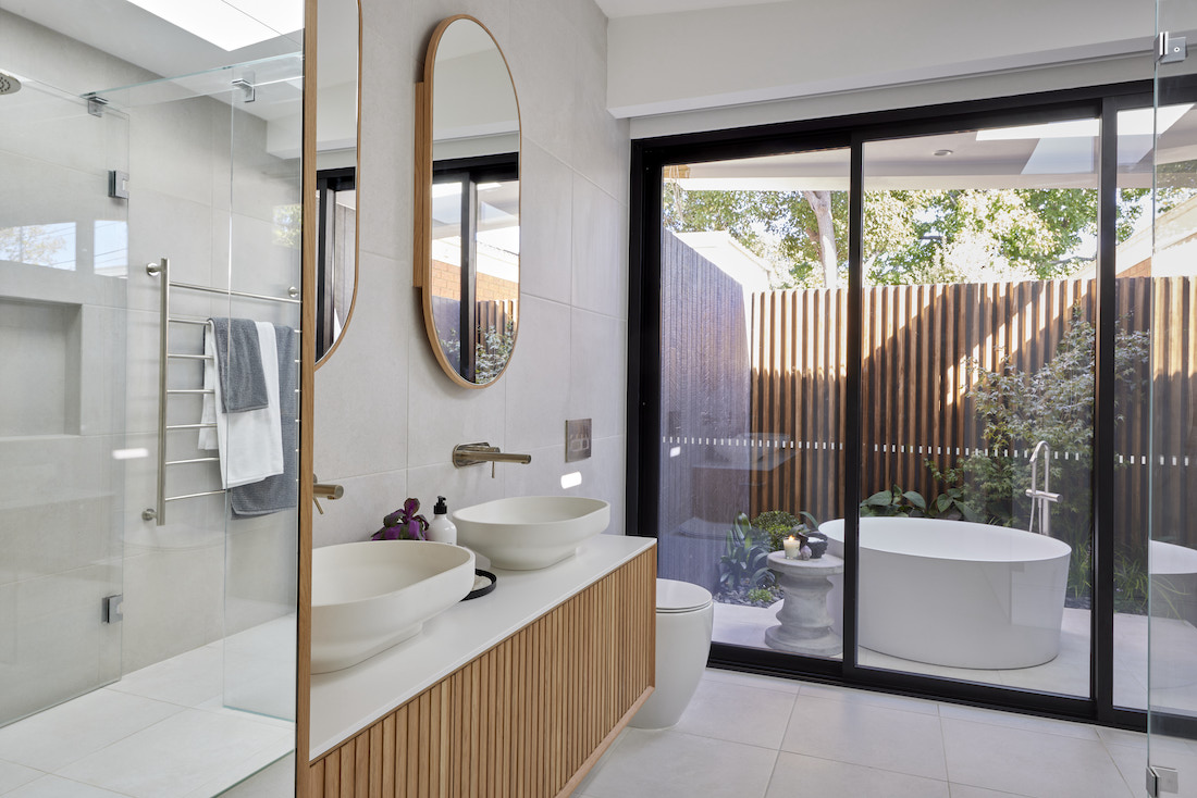Pill shaped shaving cabinet above dual basin vanity