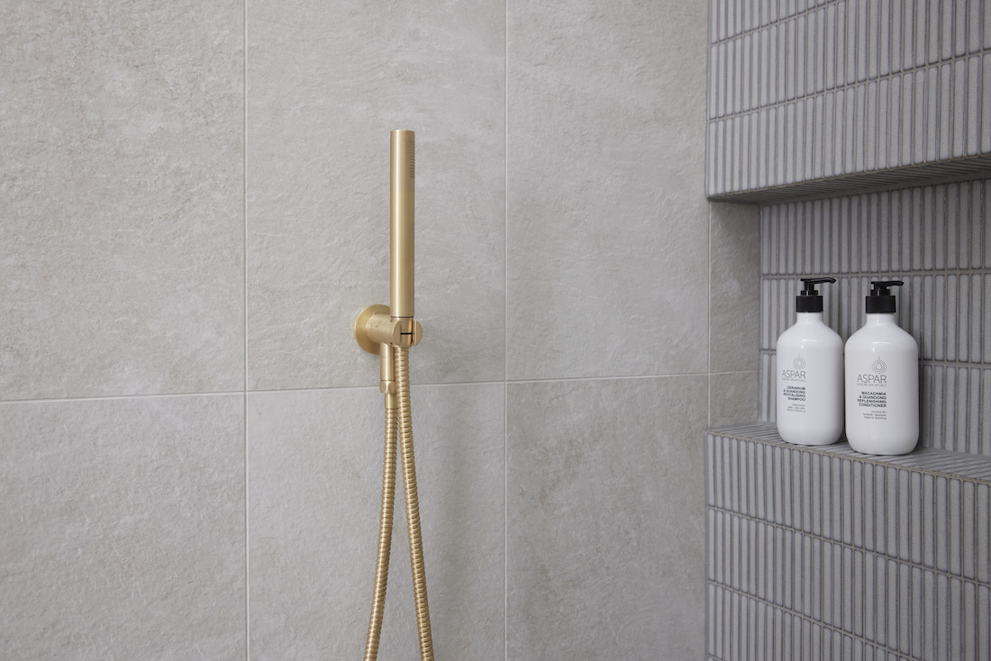 Grey tiled wall with kitkat tiles and gold tapware