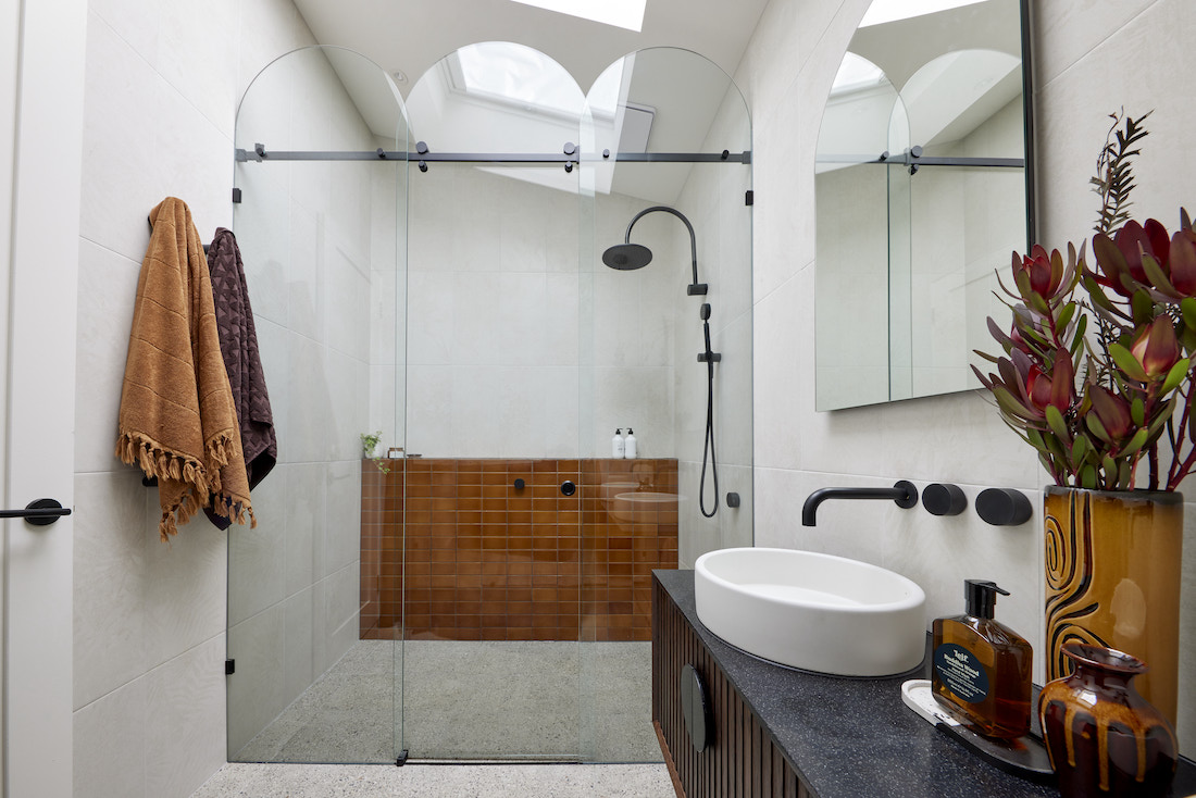 Arched shower screen with brown feature wall