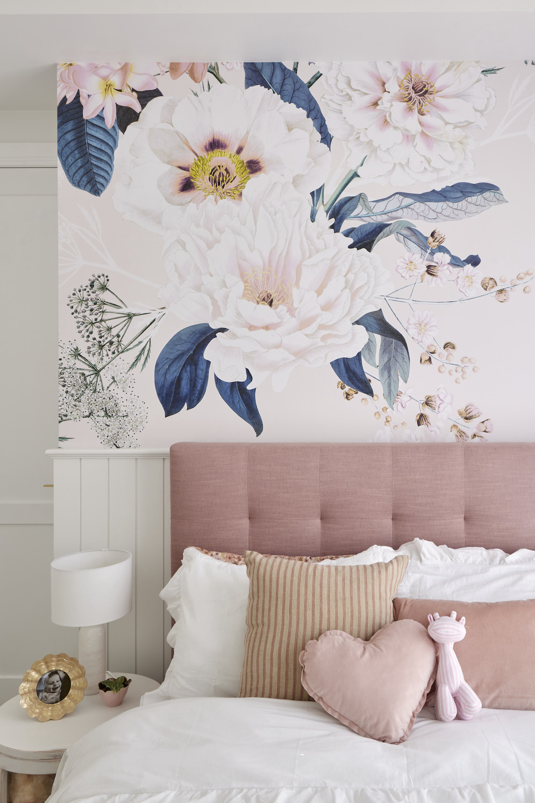 Pink padded be with floral wallpaper