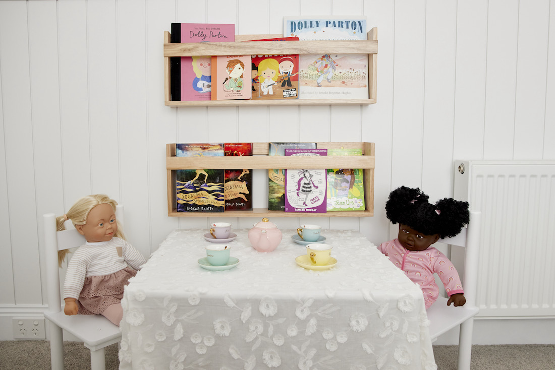 Bookshelf with dolls in kids bedroom