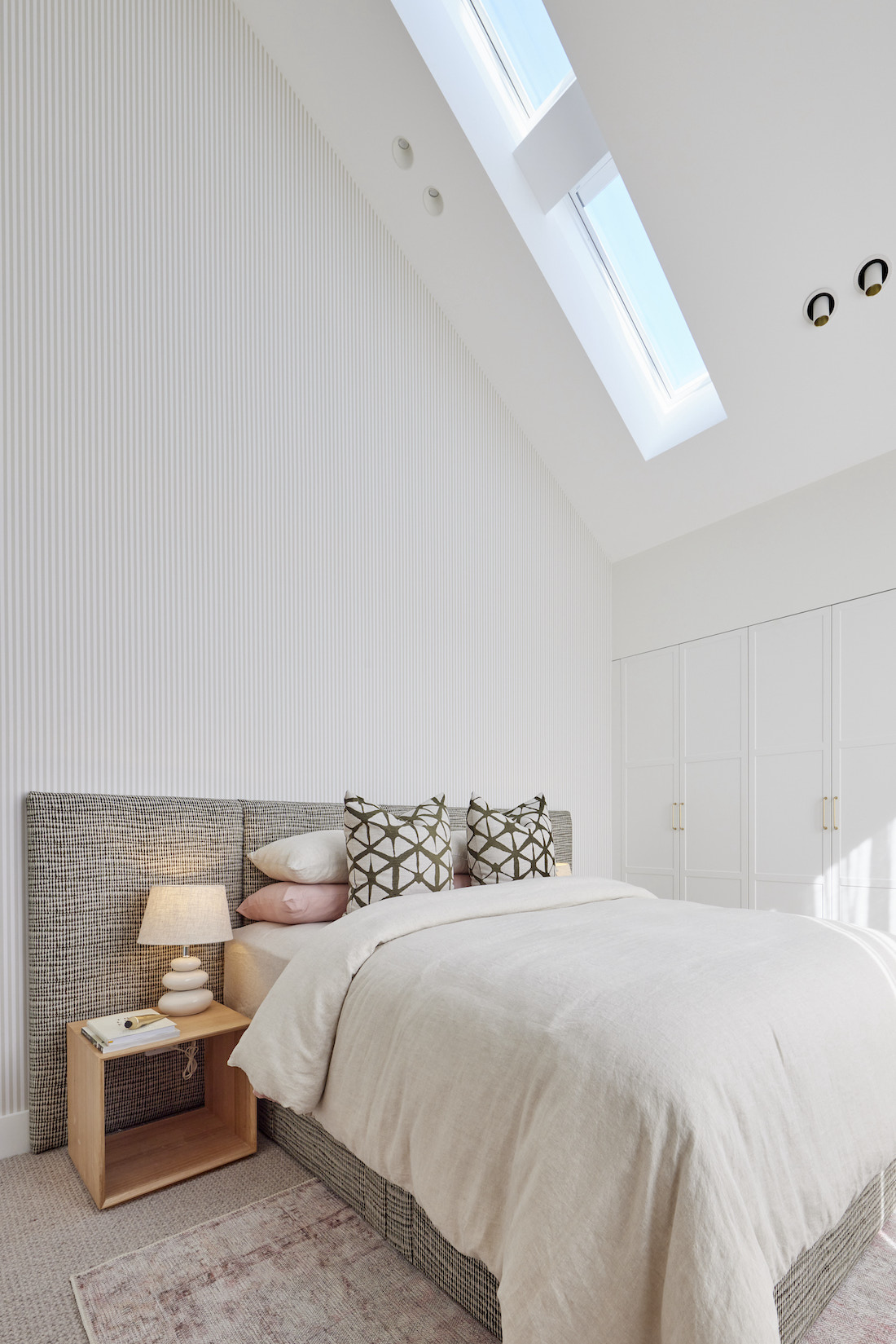 Bedroom with fabric bedhead and skylights