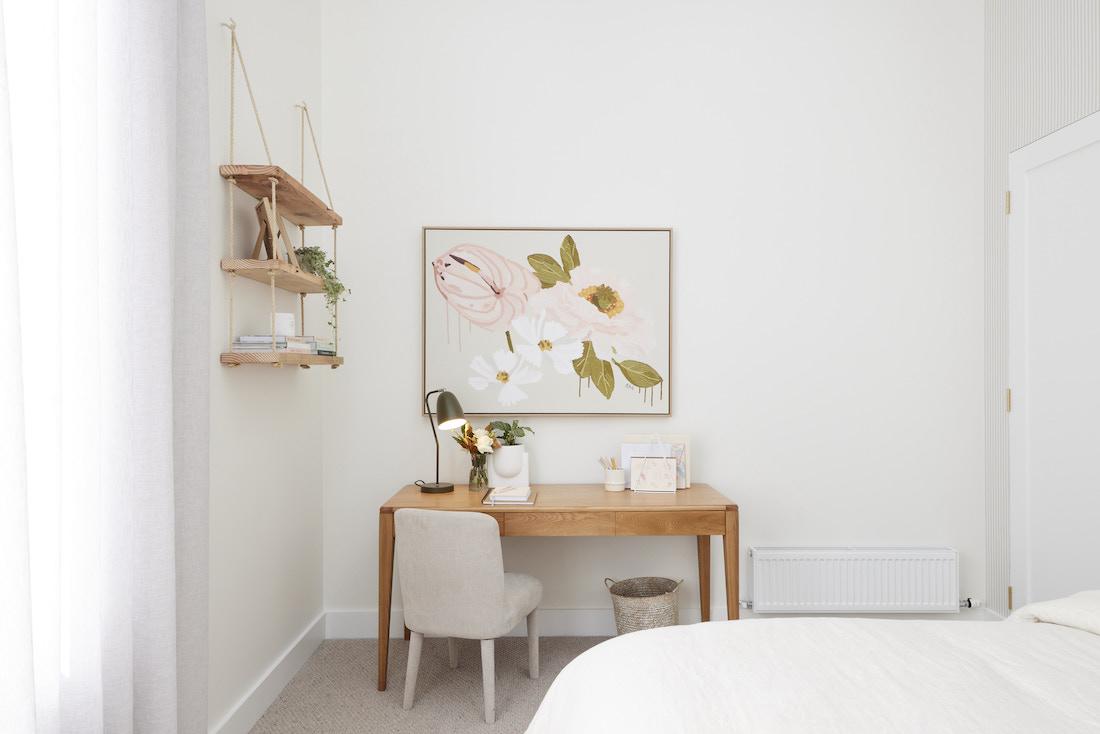 Desk space in bedroom with floral artwork