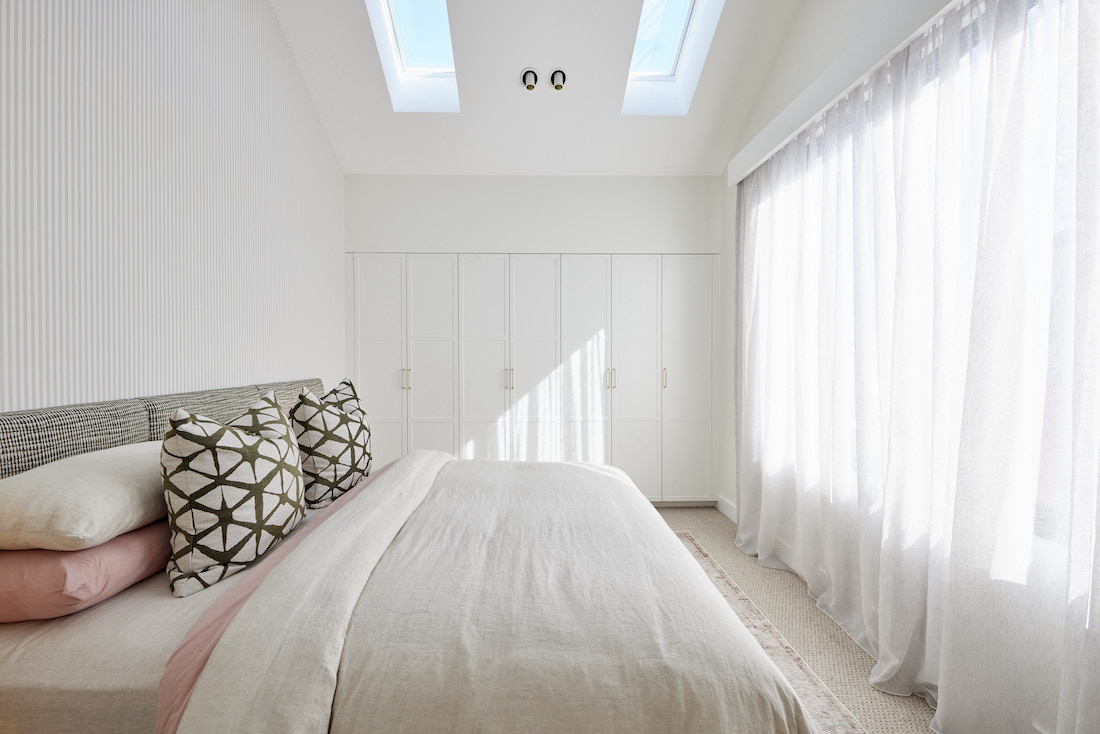 Bedroom with skylights and built-in wardrobe