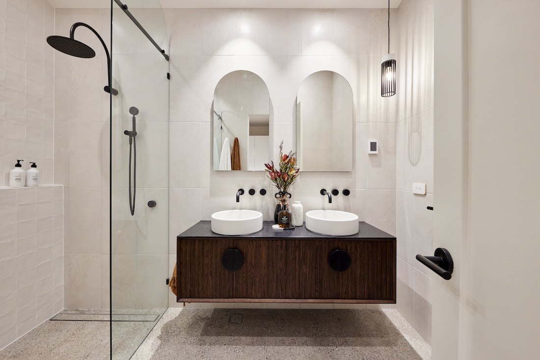 Dark timber vanity with arch mirrors
