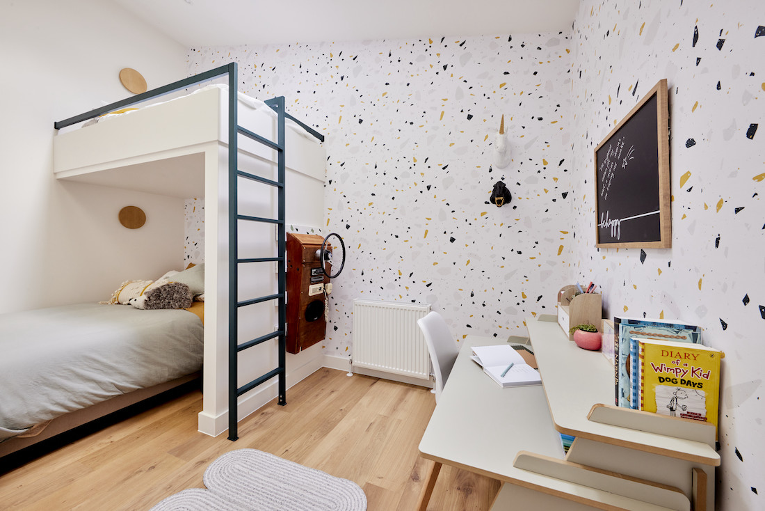 Bunk bed with ladder and flecked wallpaper