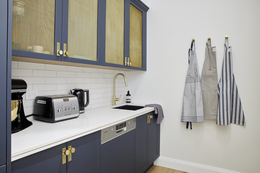 Navy cabinetry with brass insets