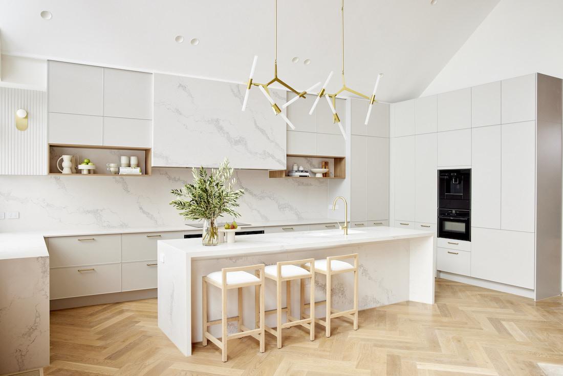 White stone kitchen with gold bar chandelier