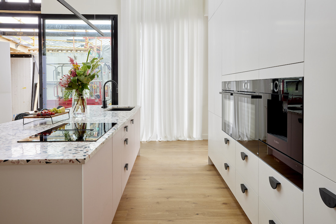 Timber flooring in white kitchen with black accents