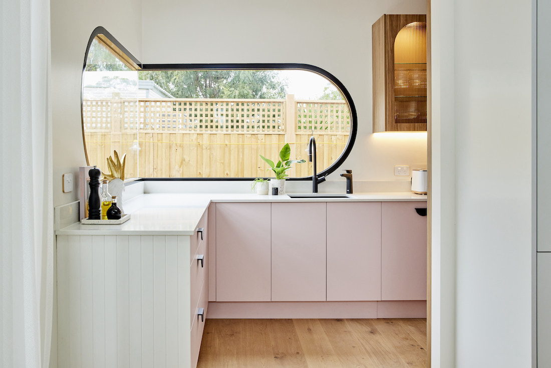 Pink cabinetry in butlers pantry with curved window
