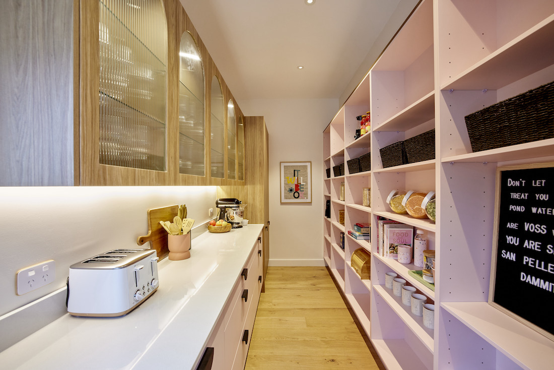 Pink shelving in butlers pantry with fluted glass cabinets