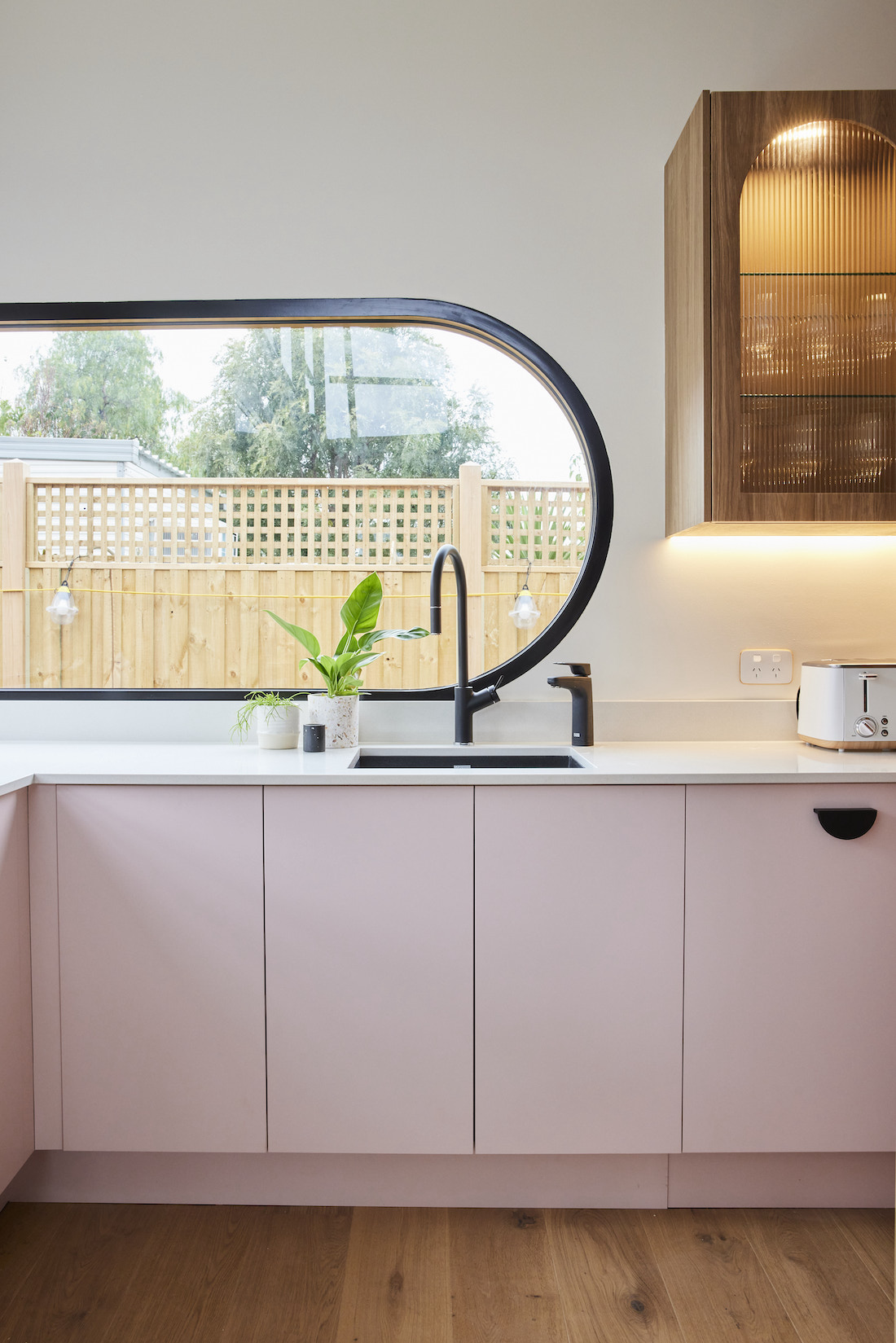 Curved window in butlers pantry with pink cabinetry