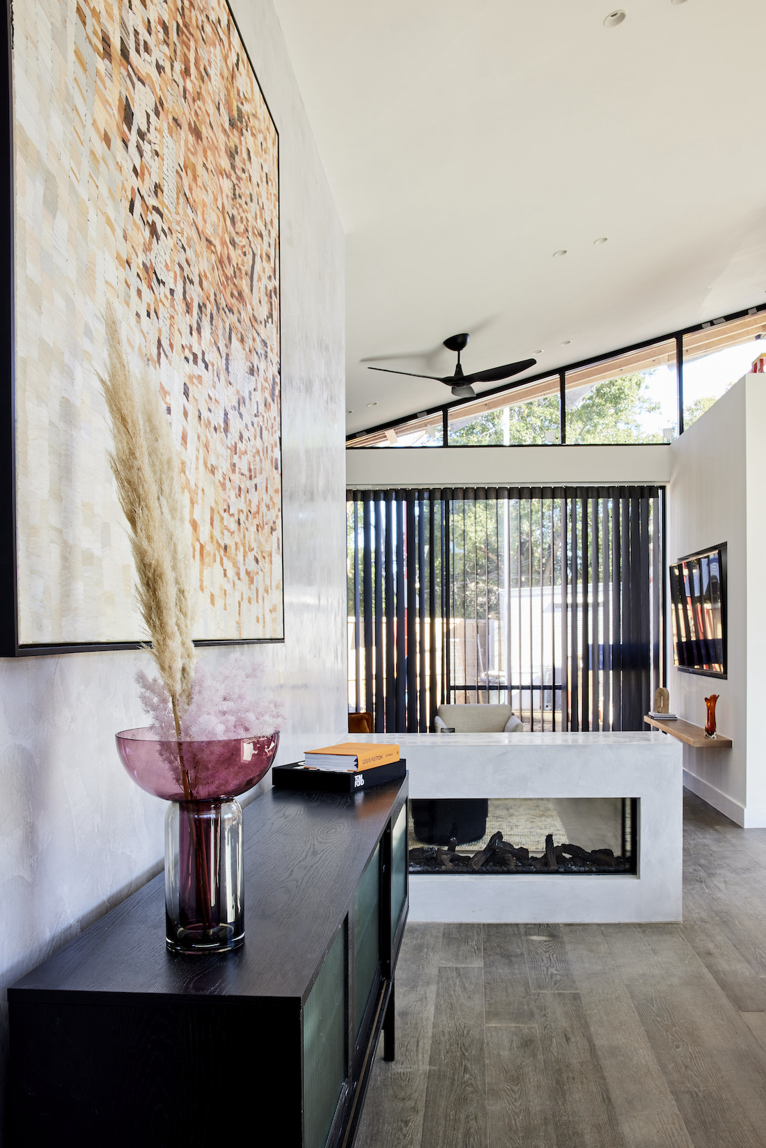 Low-walled glass fireplace with black sheer curtains