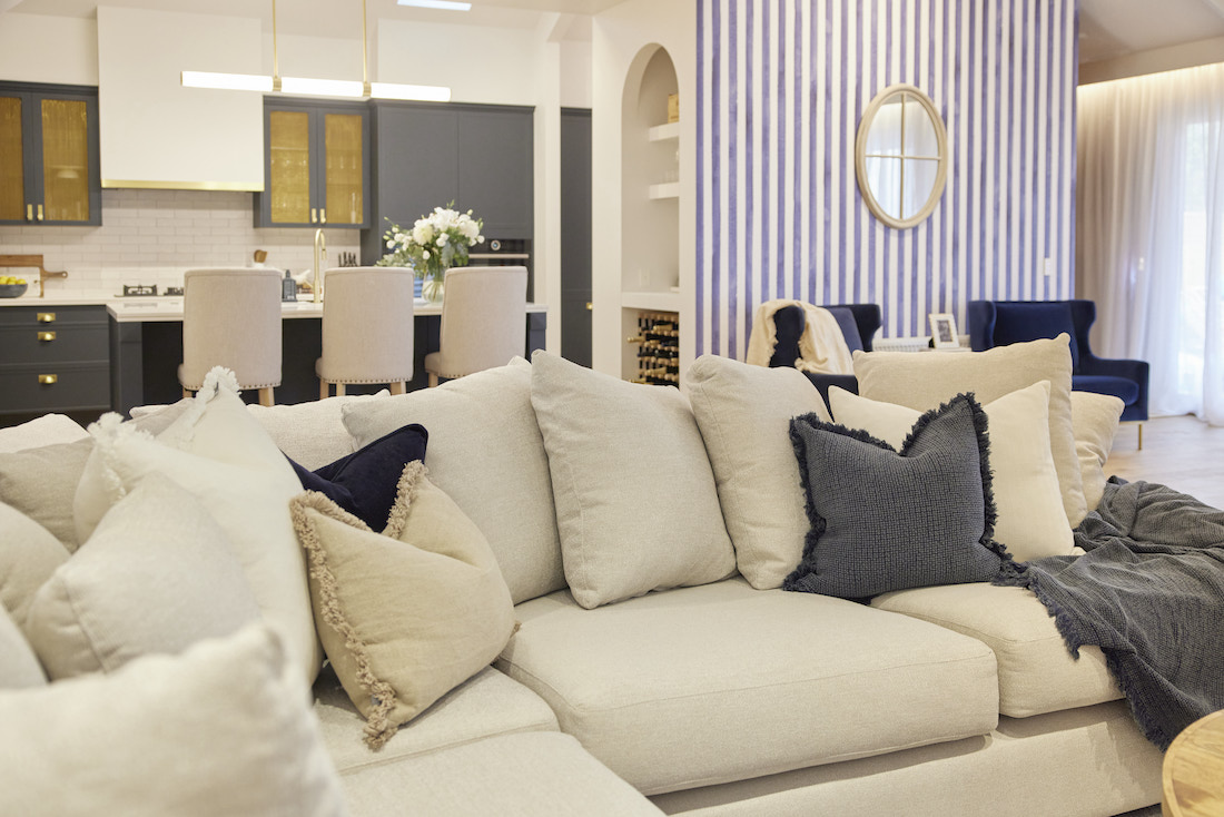 Couch with extra cushions and blue striped wall