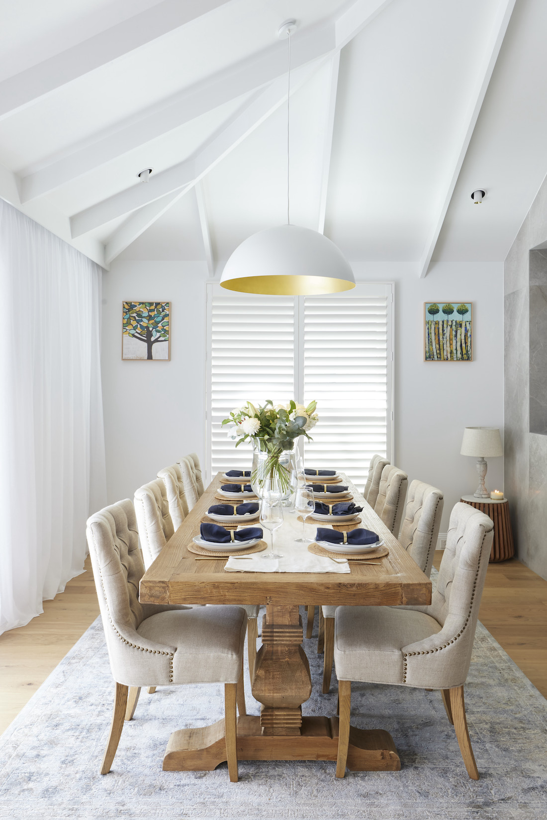 White dome light in raked ceiling above dining table