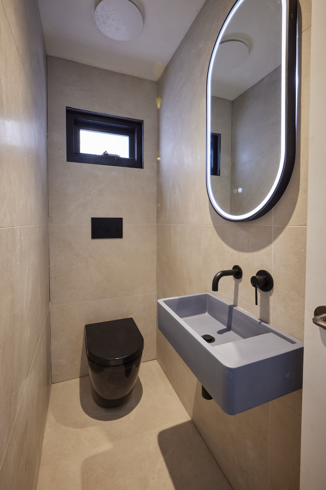 Powder room with black toilet blue basin and LED pill mirror