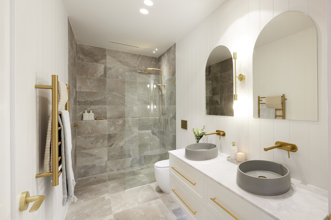 Bathroom with arch mirrors and grey tiled shower