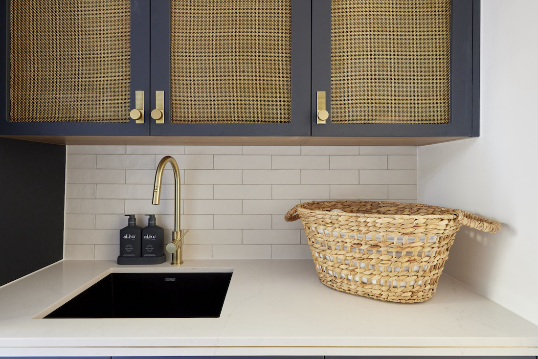 Brass inset panels in laundry cabinetry