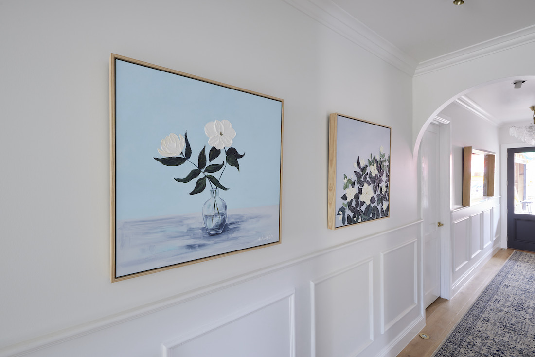 Artwork in hallway with wainscotting