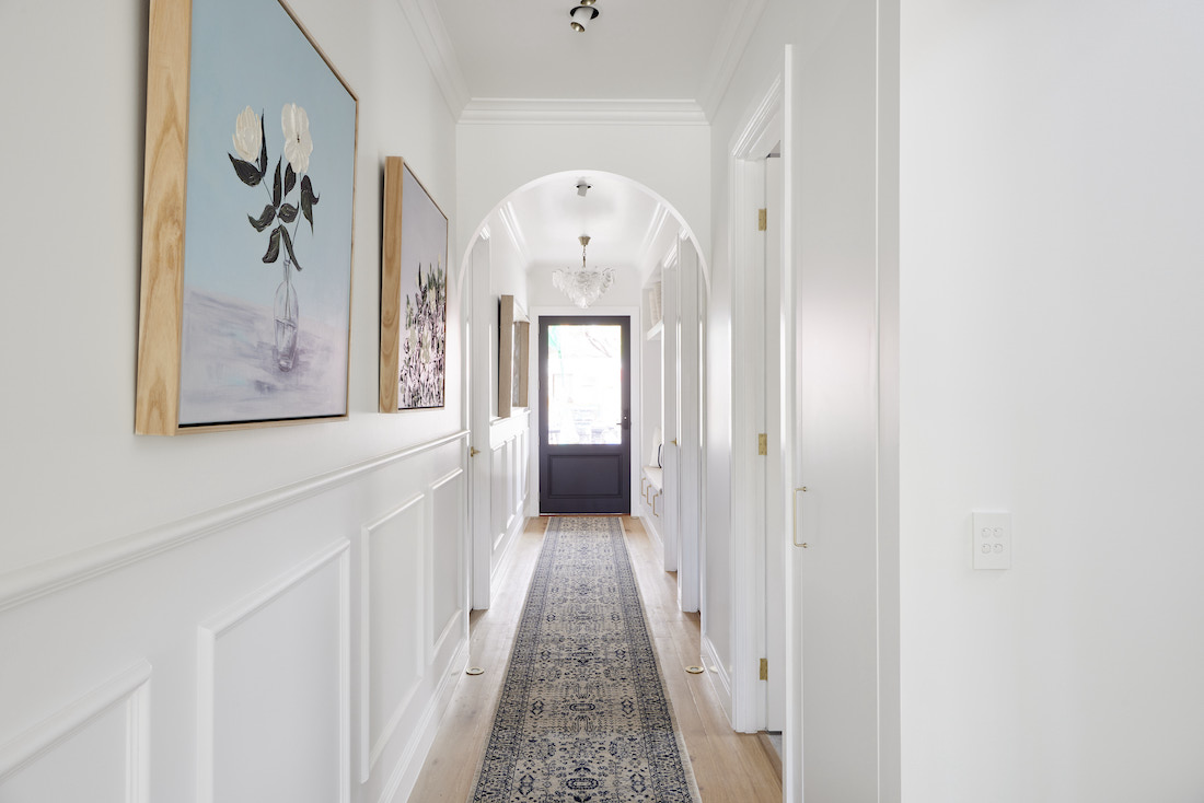 Hallway with arched doorways and wainscotting