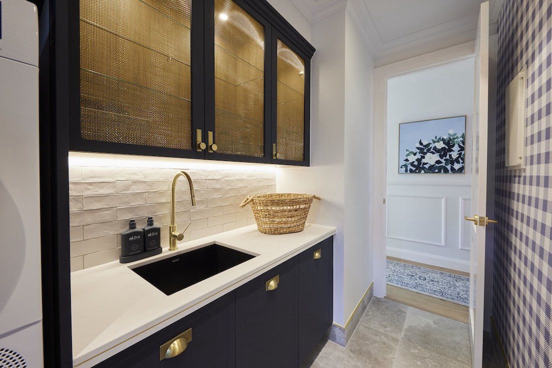 Laundry with navy cabinetry and brass inset