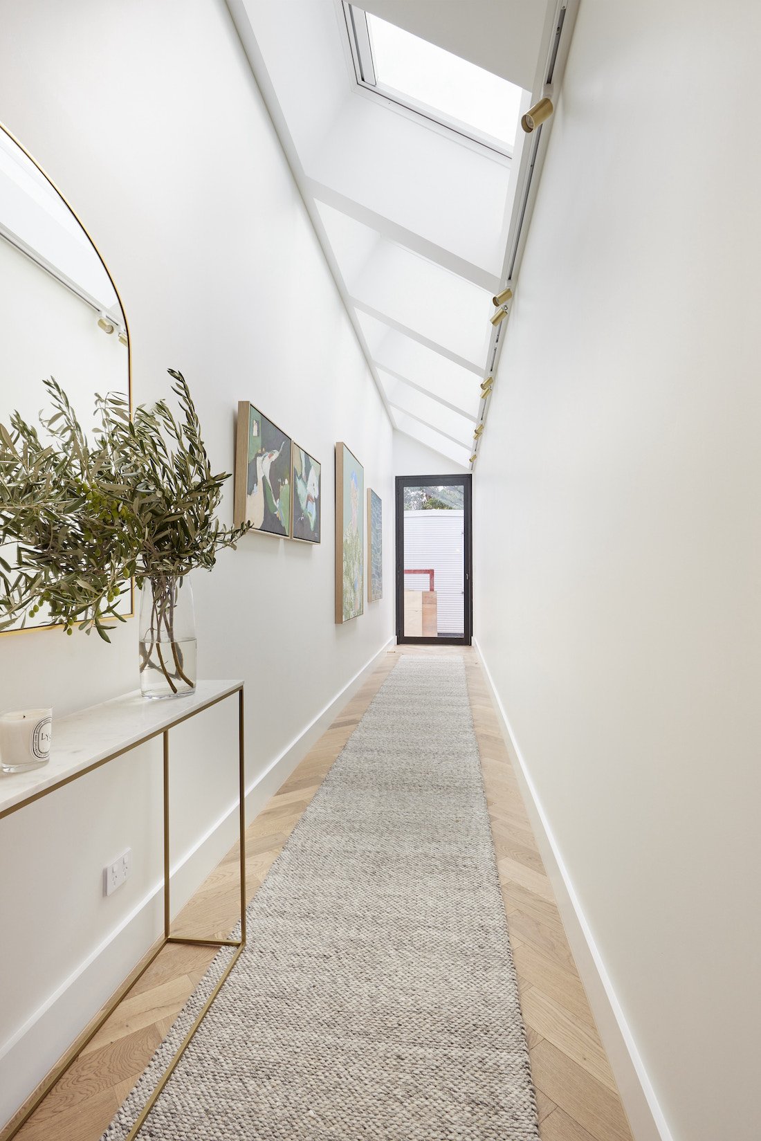 Console table in hallway with skylights