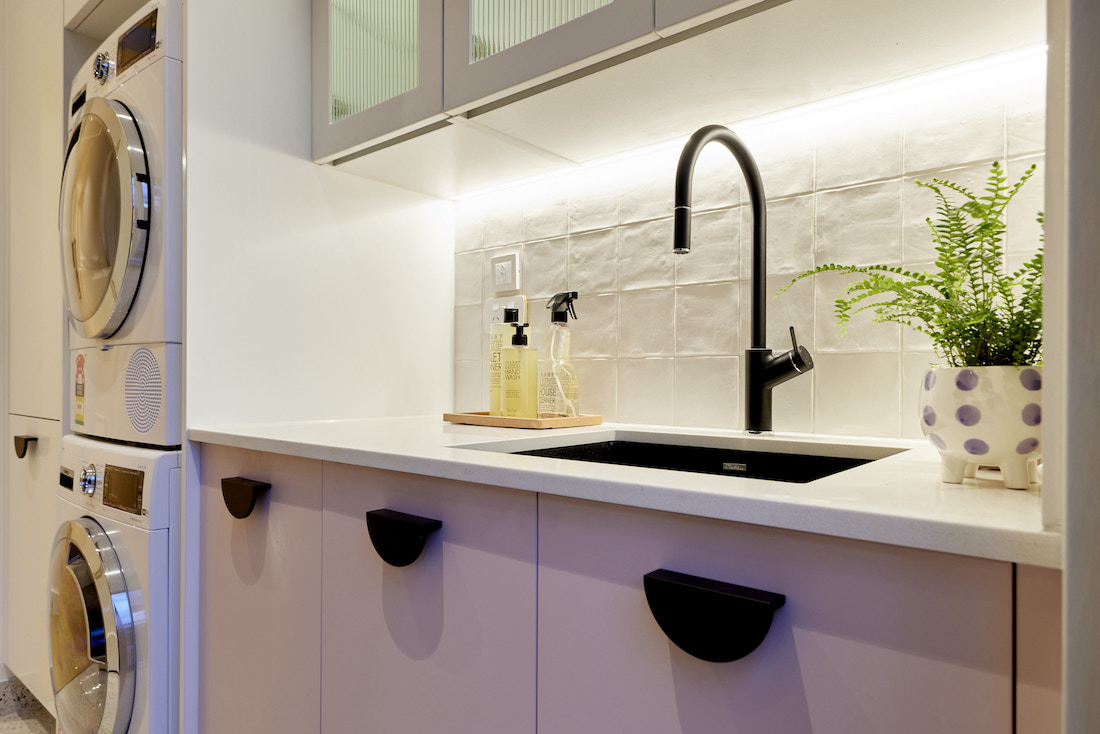 Pink cabinetry and black tap in laundry