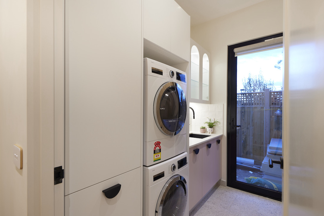 Laundry with arched fluted cabinetry and pink lowers