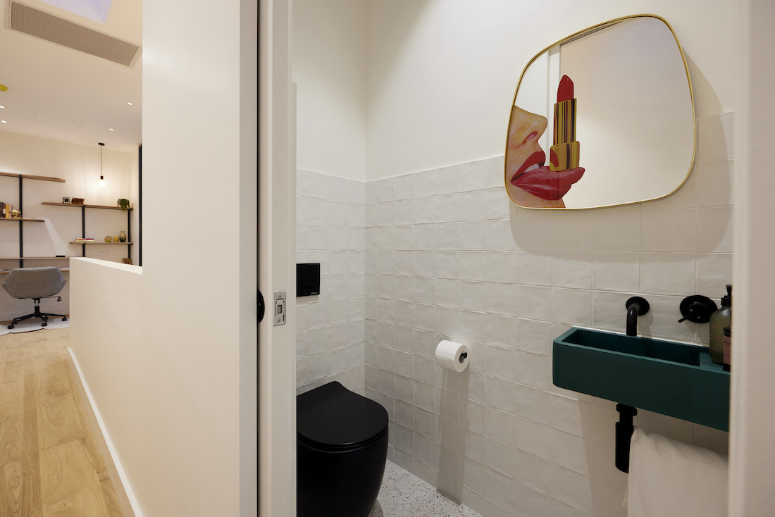 Black toilet, green basin and mirror with mouth and lipstick